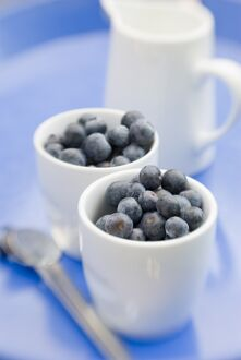 Fresh blueberries in little white pots with jug of milk or cream credit: Marie-Louise