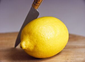 Whole fresh lemon with knife on cutting board credit: Marie-Louise Avery /