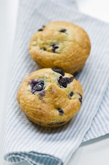 Freshly baked blueberry muffin on blue striped napkin. credit: Marie-Louise Avery