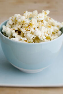 Freshly popped pocorn in pretty blue bowl credit: Marie-Louise Avery / thePictureKitchen