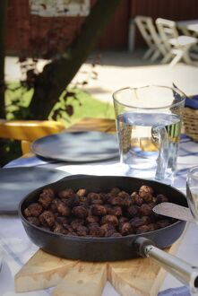 Frying pan of Swedish meatballs on table outside in dappled summer sunshine credit