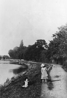 Two girls playing by the river bank, one girl with her hoop ready for rolling