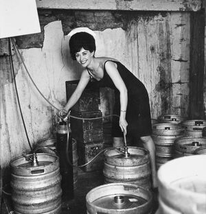 Glamour in the cellar as barmaid Lois taps another barrel of beer. 19 October 1963