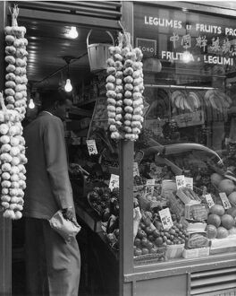 A grocer selling a variety of exotic fruit and legumes with a window sign in multiple
