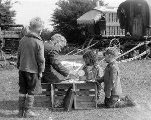 Gypsy children watching a man painting their caravan camp on Epsom Downs , Surrey