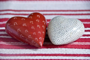 Two heart shaped soapstone paperweights, on striped table runner. credit: Marie-Louise