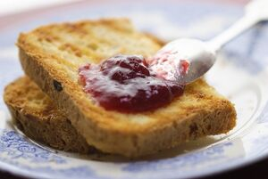 Home made jam on toast made from gluten free bread with silver spoon