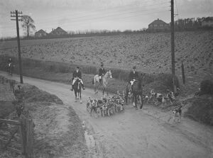 The huntsmen and their hounds follow the scent down the road. 31 January 1938