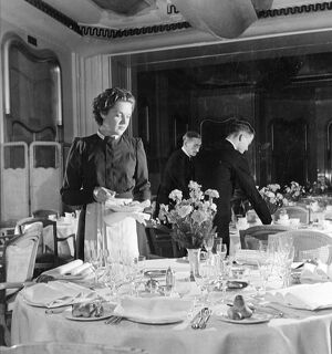 Irene Heckman, a waitress at the Lyons Trocadero, lays extra table settings on the