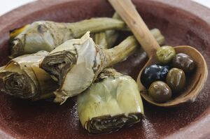 Italian grilled and marinated artichokes on brown dish credit: Marie-Louise Avery