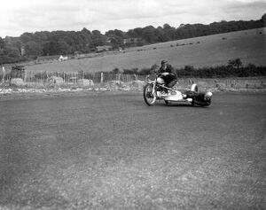 John Surtees hangs over the motorcycle side - car to balance the wheel as his father
