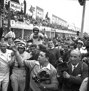 John Surtees and Lorenzo Bandini are mobbed by spectators after the finish of the
