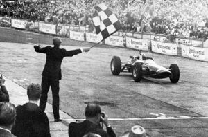 John Surtees roars across the finish line in his Ferrari to win the German Grand