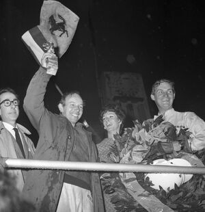 John Surtees smiles as he waves his trophy from the Victory Rostrum after he had