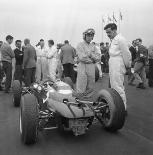 John Surtees stands next to his Lola Climax awaiting the start of the Goodwood