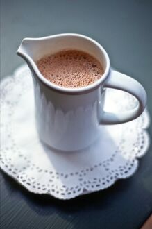 Jug of hot drinking chocolate on white paper lace doiley credit: Marie-Louise Avery