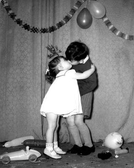 A little boy and girl kissing under the mistletoe at a Christmas party