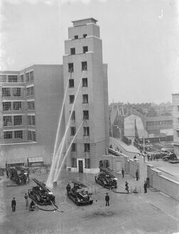 A London Fire Brigade display in Lambeth, London. Firemen hose down from the windows