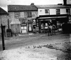 Man on horseback in front of grocer's shop around Sevenoaks area, Kent. Advertisements