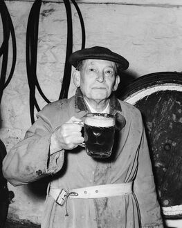 Man with a pint of beer at the Blue Anchor in Helston, Cornwall, England. 11 April 1956