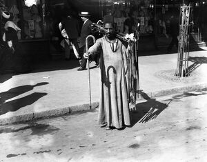 A man selling walking sticks on the streets of Cairo, Egypt. 21 March 1923