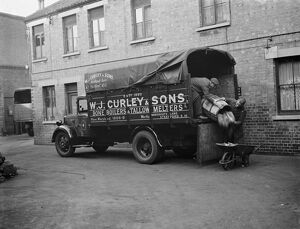 Men unloading bones and animal waste from a WJ Curley ' s lorry at Stratford, East London