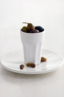 Mixed Italian olives in tall white ceramic pot on white plate with stones on white