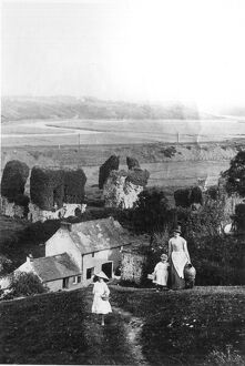 A mother and her girls climb the steep hill at the back of their garden to fetch water
