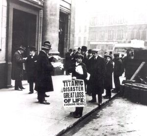 A newspaper boy spreads the news of the sing of the Titanic to bystanders outside