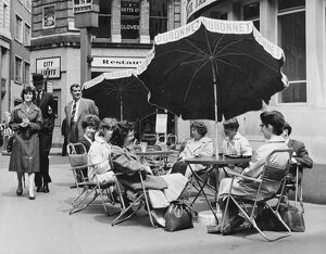 Office girls take their lunch break al fresco in a continental style table and umbrella