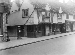 The old cock house shop at Eton, showing the old stocks and pillar box of years ago