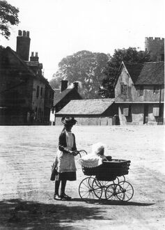 An older sister taking out the baby in a perambulator on a summer's day walk taking