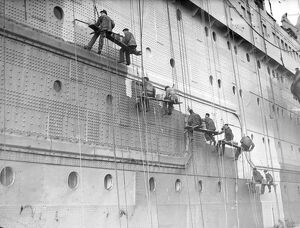 Painters are at work on the huge task of painting the hull of the Cunard White Star