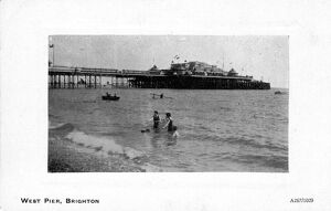 Some people swimming in the sea near West Pier, Brighton, East Sussex, England