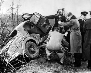 Police and photorgraphers are seen with the wreck of the black Jaguar car in which