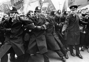 Policemen struggle to hold back the surging tide of demonstrators pressing on the