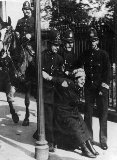 Political - four policemen, one mounted, arrest a suffragette