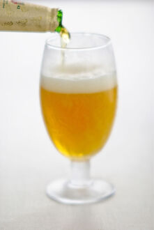 Pouring lager beer into stemmed beer glass credit: Marie-Louise Avery / thePictureKitchen