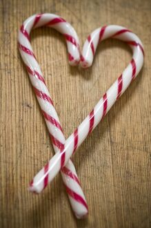 Two red and white striped candy canes on wooden surface crossed to make heart shape