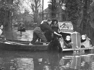 Rescue comes by boat to the occupants of a marooned car in a flooded road at Maidenhead