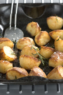 Roast potatoes in black roasting tin with salt and rosemary credit: Marie-Louise