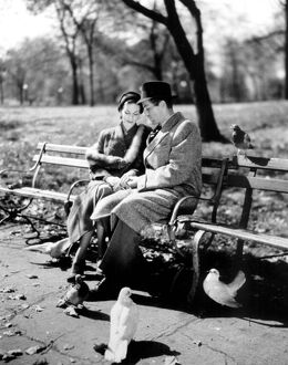 Romantic cliched couple. 1950's. Couple having a quiet moment in the park