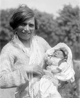 A Romany gypsy mother holds her baby at the Epsom Races . Late 1940s , early 1950s