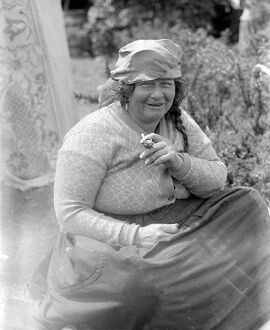 A Romany gypsy woman smoking her pipe at the Epsom Races . Late 1940s , early 1950s