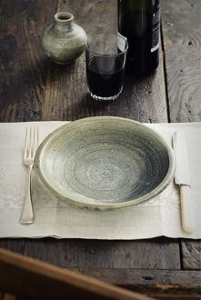 Rustic table setting with tumbler of red wine before food arrives credit: Marie-Louise