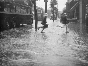 Schoolchildren running through the floods at the junction of Forest Road and Chingford