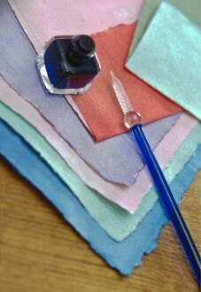 Selection of pastel coloured handmade papers with glass pen and small bottle of ink