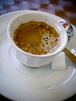 Small handleless cup of strong Turkish coffee on cafe table credit: Marie-Louise
