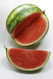 Small watermelon on white surface with quarter cut out showing red flesh credit