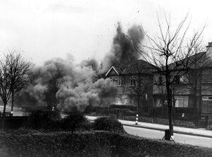 Smoke and debris thrown skywards after a direct hit from a German bomb in the suburbs
